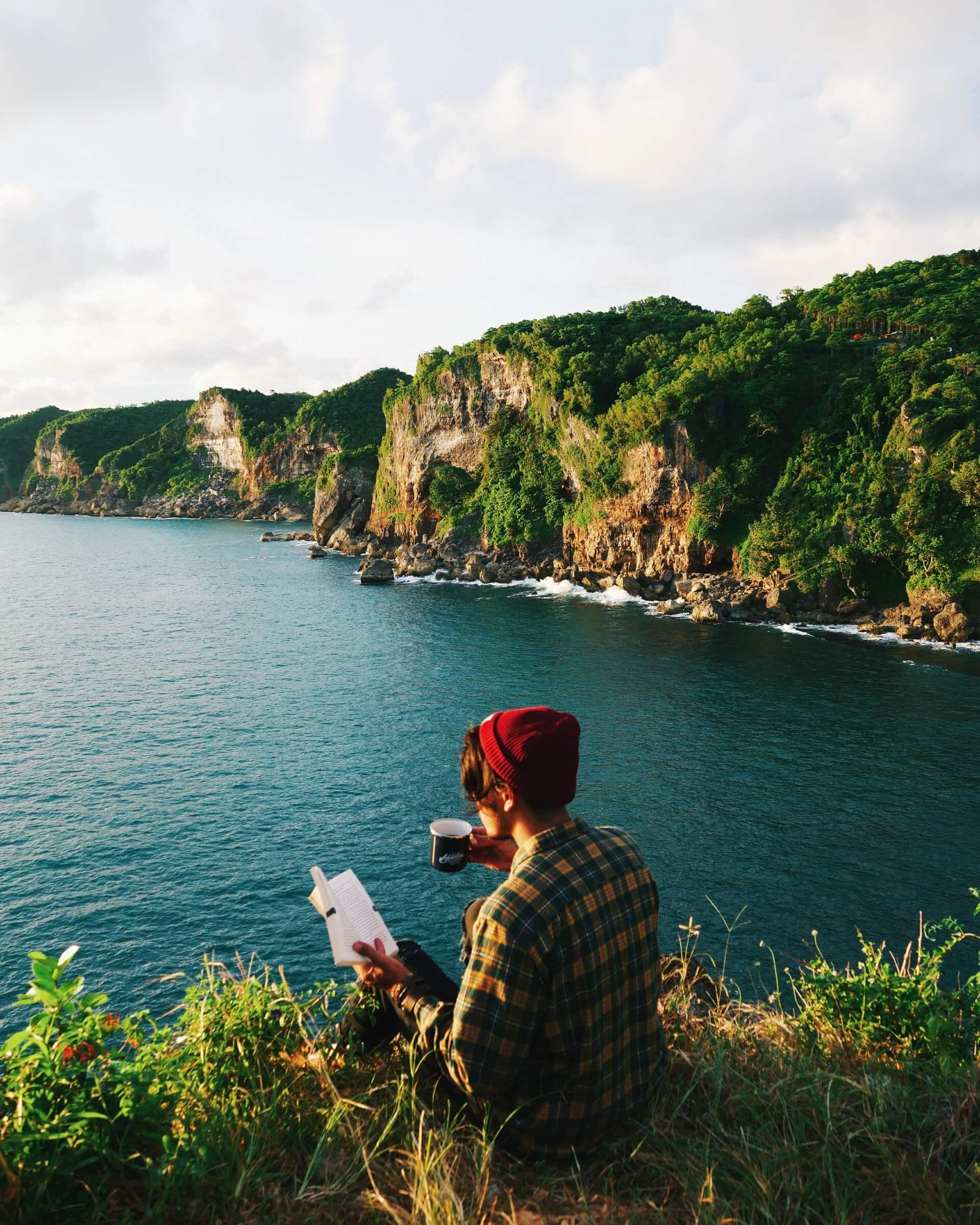 Denize karşı kitap okurken kahve içen genç