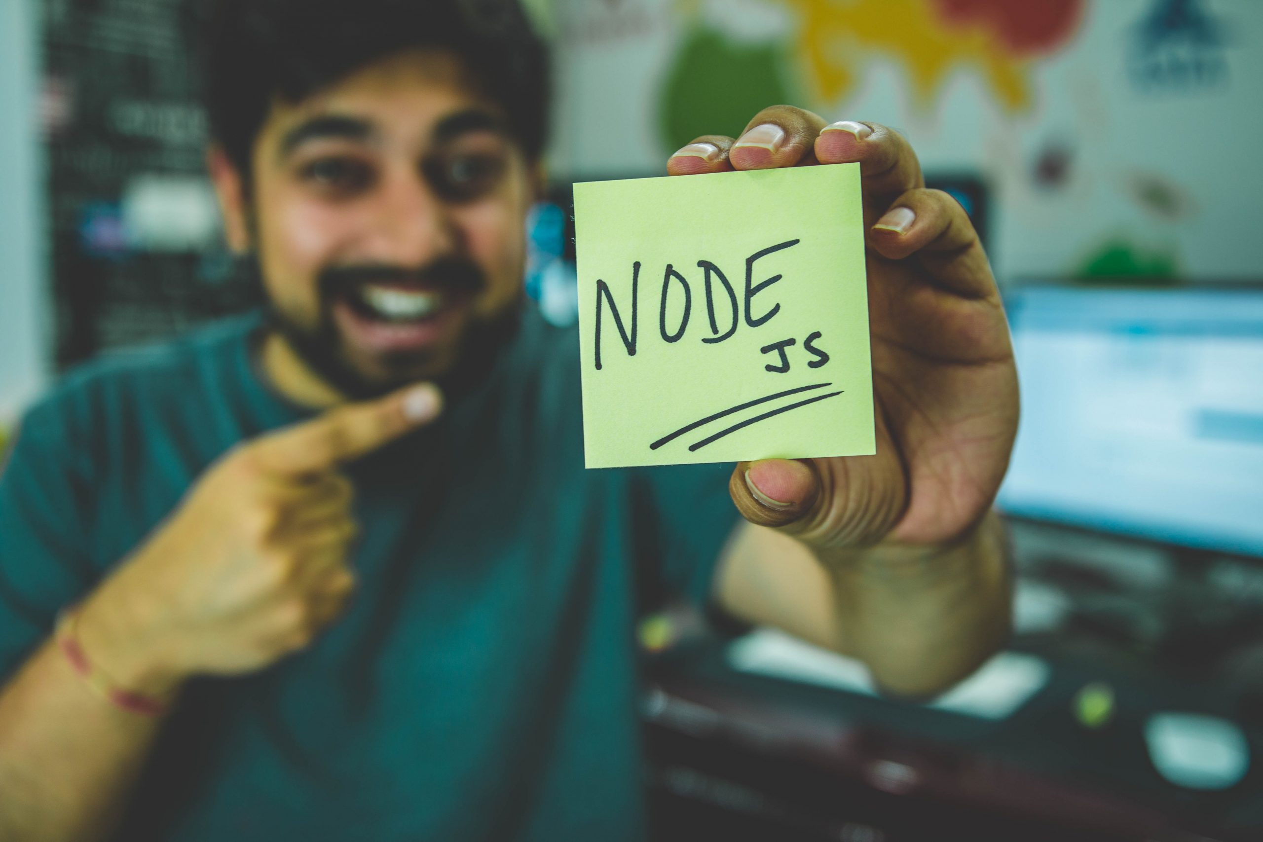Kağıtta Node jS yazısı gösteren erkek